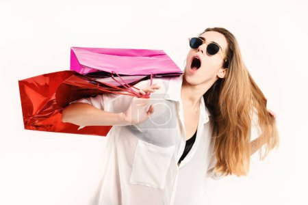 Lady holds red and pink shopping bags. Woman with packages