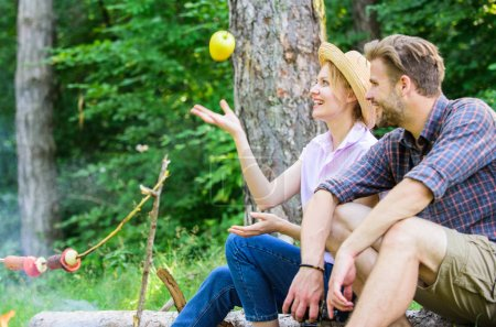 Photo for Pleasant smell of roasted food makes picnic atmosphere perfect. Picnic roasting food over fire. Couple in love relaxing sit on log having snacks. Family enjoy weekend in nature. Idyllic picnic date. - Royalty Free Image