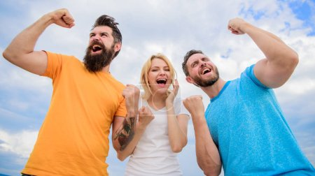 Photo for Unbelievable luck. Threesome winners happy with raised fists. We are winners. Woman and men look emotional successful celebrate victory sky background. Behavior successful team. Emotional explosion. - Royalty Free Image