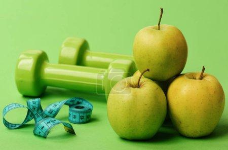 Photo pour Ruban à mesurer de couleur cyan près des cloches et des pommes juteuses, fermer. Haltères de couleur vive, ruban à mesurer et pyramide de fruits sur fond vert. Symboles de régime sain. Athlétisme et concept de poids - image libre de droit