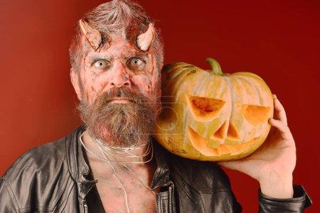 Photo pour Démon avec des cornes et des cales de visage blême de peur sculpté jack o lanterne. Concept de partie de Halloween. Diable ou monstre avec des décorations d'octobre. Homme effrayant maquillée tient citrouille sur fond rouge sanglante - image libre de droit