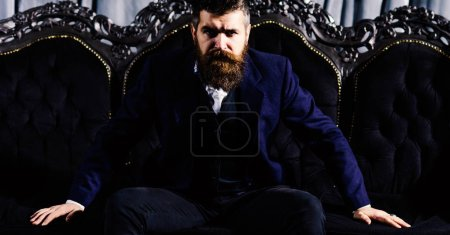 Photo for Handsome bearded man with colorful tubes in long beard and mustache has stylish hair on funny face holding glass of alcoholic cocktail in vintage suede leather waistcoat on blue studio background. - Royalty Free Image