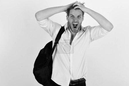 Photo pour Homme au visage excité ou en colère et aux cheveux désordonnés porte un sac à dos isolé sur fond blanc. Concept de voyage et de tourisme. Homme en chemise rose avec sac à dos sur l'épaule. Backpacker va randonnée - image libre de droit