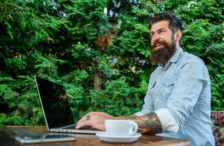 Photo for Hipster freelancer work online blog notebook. Man bearded businessman sit terrace with laptop and cup of coffee. Freelance benefit. Create content for web blog. Blogger create post while enjoy coffee. - Royalty Free Image