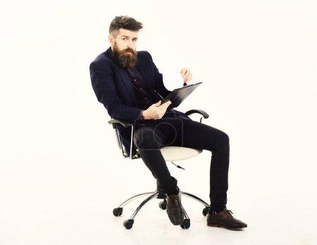 Foto de Concepto de trabajo. Encargado se sienta en la silla de la oficina y tiene papel obra. - Imagen libre de derechos
