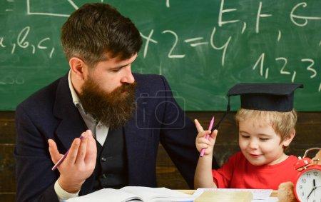 Photo pour Père enseigne les mathématiques fils. Un gamin joyeux étudiant avec un prof. Concept de leçon d'arithmétique. Enseignant en tenue formelle et élève en mortier en classe, tableau sur fond . - image libre de droit