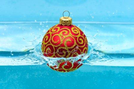 Foto de Concepto de vacaciones y vacaciones. Decoración festiva para la bola de árbol de Navidad, rojo con brillo decoración se ha caído al fondo de agua azul. Decoración de la Navidad o juguete para árbol de Navidad de nadar en la piscina. - Imagen libre de derechos
