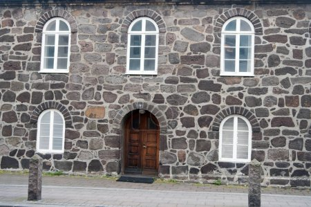 Old stony building with windows. Wall made out of big stones. Old building material concept. Ancient stony house or part of defenses. Building with thick walls and heavy wooden front door.