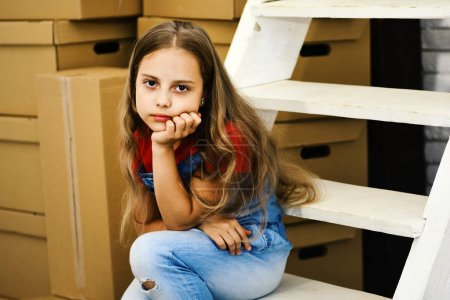 Photo for Kid sits on white ladder by pile of cardboard boxes. Child with bored or sad face. Girl with fair wavy hair on room background. Moving in or out and new home concept - Royalty Free Image