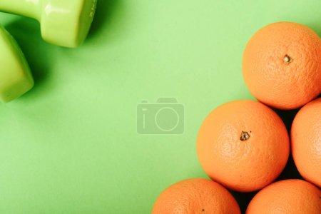 Photo pour Symboles de sport et mode de vie sain, espace de copie. Modèle composé de fruits orange près des cloches de couleur verte. Régime alimentaire et sport concept de régime. Oranges près des haltères sur fond vert, vue de dessus - image libre de droit