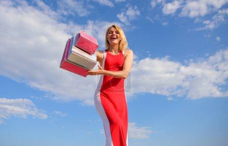Photo pour Robe rouge femme porte tas de sacs à provisions fond bleu ciel. Enfin acheté des marques préférées. Fille satisfaite du shopping. Conseils boutique soldes d'été avec succès. N'hésitez pas à acheter tout ce que vous voulez . - image libre de droit