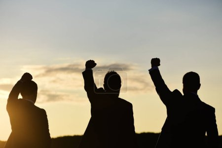Photo for Silhouettes of men putting their fists up. Victory and business success concept. Male dark figures expressing confidence and leadership. Businessmen in formal wear on sunset sky background - Royalty Free Image