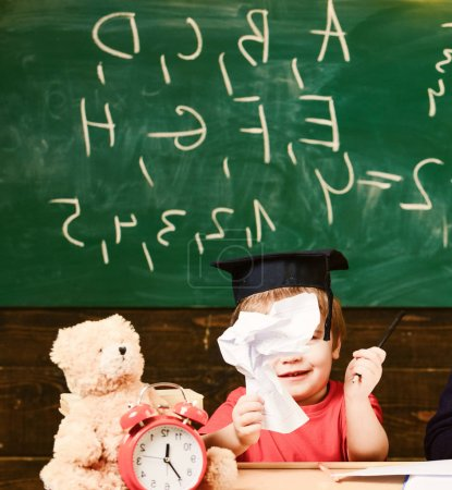 Photo for Cute boy wearing academic cap in the classroom. Little child holding paper figure. Smiling kid sitting at the desk in front of the green board. - Royalty Free Image