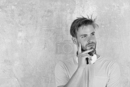 Photo pour Américain beau barbu avec écouteurs. L'homme européen passe du bon temps. Joyeux adolescent DJ écouter des chansons via des écouteurs. Style de vie musical. Hipster élégant aux yeux bleus avec smartphone . - image libre de droit