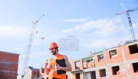 Photo for Man orange vest and helmet works at construction site. Contractor control according to plan. Control construction process. Guy in protective helmet stand in front of building made out of red bricks. - Royalty Free Image