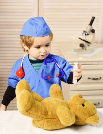 Photo for Boy in surgical uniform holds syringe on wooden background. Medical education and childhood concept. Little vet with serious face playing doctor. Kid in doctor coat makes injection to teddy bear - Royalty Free Image