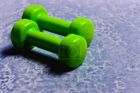 Photo for Sports and healthy lifestyle concept. Dumbbells made of bright green plastic on grey texture background, close up. Barbells in light weight, close up. Shaping and fitness equipment. - Royalty Free Image