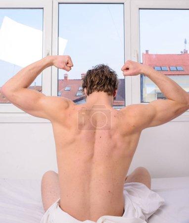 Photo pour Exercice vigoureux meilleur, mais même l'exercice léger mieux qu'aucune activité. Homme dos musclé étirant lit vue arrière. Préparez-vous au nouveau jour. L'activité physique aide à sortir du lit. Étirement du matin . - image libre de droit