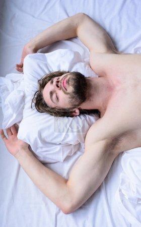 Photo pour Guy sexy macho posait des draps blancs. Homme endormi visage barbu non rasé sommeil se repose. Concept de rêve agréable. Laissez votre corps se sentir à l'aise. homme unshaven beau gars nu torse sommeil sieste sur lit . - image libre de droit
