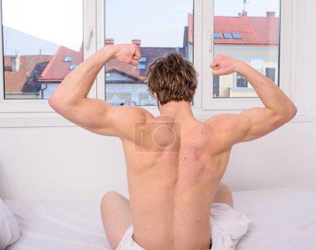 Photo pour Bonjour, les étirements. Exercice vigoureux meilleur, mais même l'exercice léger mieux qu'aucune activité. Homme dos musclé étirant lit vue arrière. Préparez-vous au nouveau jour. L'activité physique aide à sortir du lit . - image libre de droit