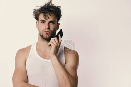 Photo for Technology and modern lifestyle concept. Man holds gadget in hands and talks on it. Guy with interested face isolated on light grey background, copy space. Man with messy hair holds mobile phone - Royalty Free Image