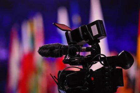 Photo pour Télévision numérique moderne ou caméra vidéo, caméscope, enregistreur en studio sur fond flou coloré. Radiodiffusion, médias, divertissement - image libre de droit