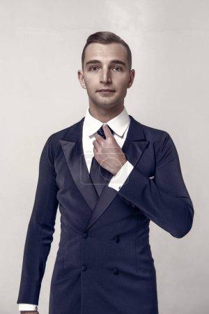 Foto de Chico joven guapo empresario o caballero con la moda del pelo en traje formal negro de chaqueta, camisa y corbata sobre fondo gris estudio - Imagen libre de derechos