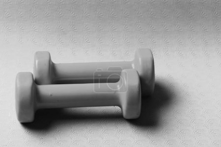 Photo for Barbells in small size, close up. Sports and healthy lifestyle concept. Shaping and fitness equipment. Dumbbells made of pink plastic on purple texture background. - Royalty Free Image