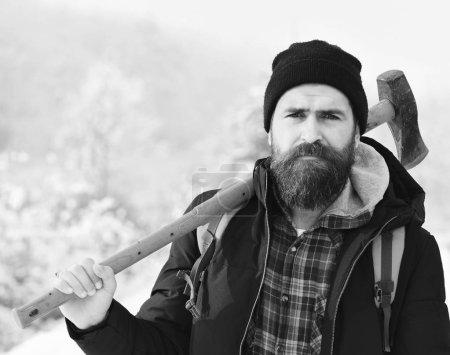 Photo pour Concept de bûcheron Hipster. Macho en vêtements d'hiver avec sac à dos et hache jaune. Homme avec barbe et moustache tient la hache. Homme au visage triste avec de la neige sur le fond . - image libre de droit