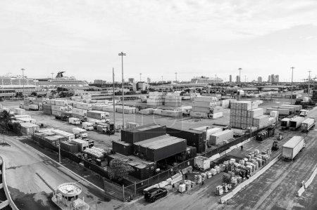 Photo pour Miami, Etats-Unis - 22 novembre 2015: port maritime ou terminal avec piles de conteneur de fret, camions sur ciel nuageux. Livraison, livrer, chargement, transport de véhicules pour le Transport entrepôt - image libre de droit