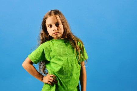 Photo pour Kid pose comme Bgirl dans un style cool. L'enfant ressemble à une star du hip hop portant des vêtements décontractés. Fille avec visage confiant sur fond bleu. Concept d'enfance et de style de vie. - image libre de droit