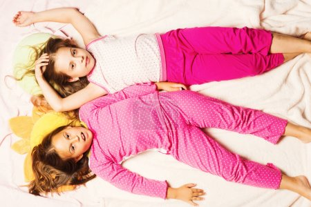 Photo pour Enfants en pyjama rose s'amusent. Enfants avec visages fatigués se situent aux oreillers et fond de couverture rose légère. Écolières ayant pyjama partie, vue de dessus. Concept de l'enfance, de fête et de bonheur. - image libre de droit