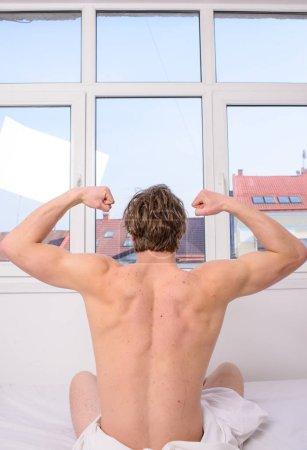 Photo pour Homme dos musclé étirant lit vue arrière. Préparez-vous au nouveau jour. L'activité physique aide à sortir du lit. Bonjour, les étirements. Exercice vigoureux meilleur mais même léger exercice mieux qu'aucune activité . - image libre de droit