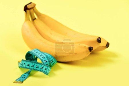 Photo pour Ruban de mesure en couleur turquoise à côté de tas de bananes, isolés sur un fond jaune clair. Concept de régime de vitamine et faible en calories des aliments - image libre de droit