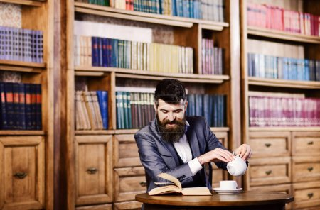 Photo for Laugh, relax, pleasure, leisure, hobby concept. Happy man sits in vintage interior and enjoys relaxing reading. Bearded man in formal outfit visits library. Mature man with smiling face has tea. - Royalty Free Image