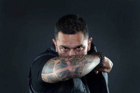 Photo for Do tattoos hide lack of masculinity. Man brutal guy cover face with tattooed arm. Tattooed elbow hide male face dark background. Visual culture concept. Tattoo can function as sign of commitment. - Royalty Free Image