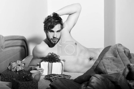 Photo for Young handsome bearded sexy macho man with stylish beard lying naked on bed under red blanket with presents or valentine gifts and shows abs with muscle torso on athletic body on colorful background. - Royalty Free Image