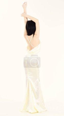 Photo pour Mariée, jeune fille en robe gracieuse. Femme en robe blanche élégante avec dos nue, fond blanc. Mannequin démontrer cher à la mode robe de soirée ou robe de mariée. Concept de mariage mode. - image libre de droit