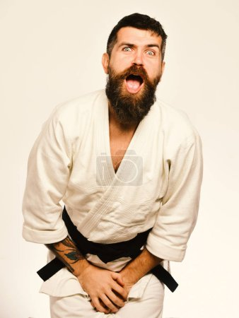 Photo for Man with beard in white kimono on white background. Training and combat concept. Jiu Jitsu master got punch into groin covering it with hands. Karate man with suffering face in uniform. - Royalty Free Image