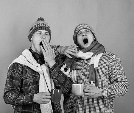 Photo pour Frères et sœurs boivent bâillement et chocolat chaud. Twins avec visages fatigués contenir tasses bruns et bleus. Saison d'automne et de l'amitié. Gars dans les écharpes tricotées et chapeaux sur fond vert clair, espace copie. - image libre de droit