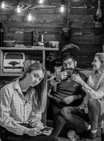 Photo pour Les parents s'amusent pendant que l'enfant au visage solitaire s'assoit seul, concept d'écart de génération. Adolescent informations de navigation sur Internet avec un nouveau gadget. Fille bavarder en ligne au lieu de la communication de la vie réelle . - image libre de droit