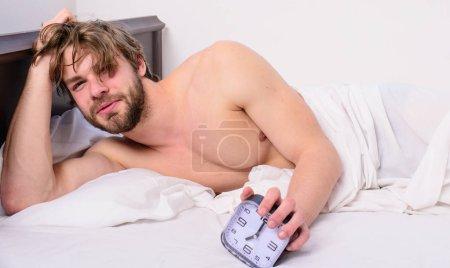 Photo pour Homme unshaven tousled cheveux visage éveillé se reposer. Bonjour. Bonjour. Homme non rasé couché lit tenir réveil. Horaire de bâton même heure de réveil au coucher. Réglez votre horloge de corps. Assez dormi pour lui. . - image libre de droit