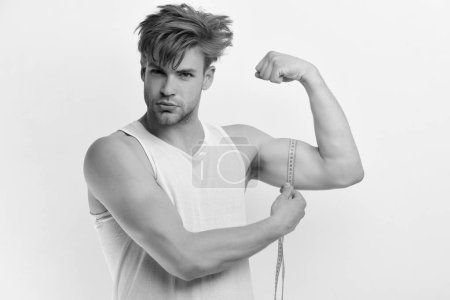 Photo pour Athlète aux cheveux sales montrant des biceps et des triceps. Concept de mesure et de style de vie sportif. Homme avec un long ruban à mesurer jaune autour du muscle. Guy au visage confiant isolé sur fond blanc - image libre de droit