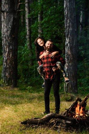 Photo pour Couple amoureux s'amuser, profiter de la liberté. Couple souriant dans la forêt, la luxure de l'errance. Concept insouciant et de liberté. Homme portant sa petite amie heureuse sur le dos, femme étreint son petit ami, forêt sur fond . - image libre de droit