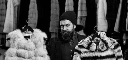 Photo pour Homme au visage délicat détient des manteaux de fourrure avec étendoir sur fond. Mec avec barbe choisit des manteaux de fourrure. Homme d'affaires avec chapeau et pardessus chers. Concept d'élégance et de glamour. - image libre de droit