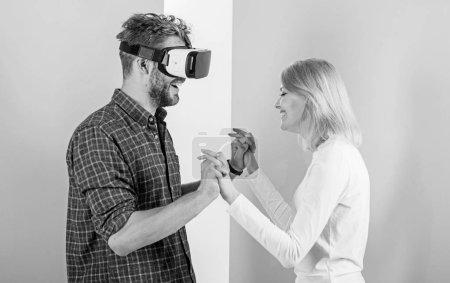 Photo pour Lunettes de Vr homme profiter de jeux vidéo. Plus beau cadeau que jamais. Homme Profitez de réalité virtuelle. Fille heureuse il comme son cadeau. Idées de cadeaux pour les hommes. Lui faire plaisir lui cadeau lunettes de réalité virtuelle et de laisser jouer jeux toute la journée. - image libre de droit