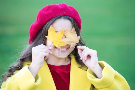 Joyfull and essentially happy. Small girl happy smiling with autumn leaves. Happy girl on autumn day. Small girl wear fashion clothing. Fashion trends for autumn. Fashionable and pretty