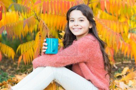 Photo pour J'ai une enfance merveilleuse. Petit enfant profiter de boisson chaude d'automne. Petit enfant se détendre à l'arbre d'automne. Joyeuses années d'enfance. Chanceux de jouer dans les arbres . - image libre de droit