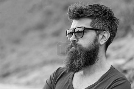 Photo pour Hipster homme dans des lunettes de soleil à la mode debout sur la pente avec verre vert luxuriant au printemps. Homme barbu avec coiffure élégante profitant de la vue sur la ville . - image libre de droit