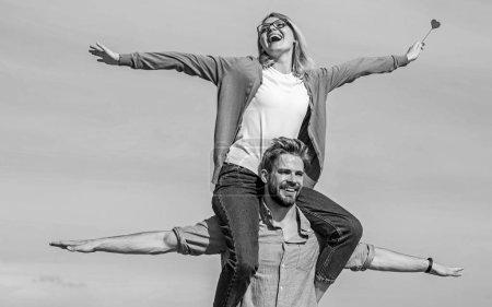 Photo pour Concept de liberté. Couple amoureux profiter de sentir la liberté journée ensoleillée en plein air. Homme porte petite amie sur les épaules, fond de ciel. Les amoureux apprécient la date et se sentent libres. Couple heureux date avoir du plaisir ensemble . - image libre de droit
